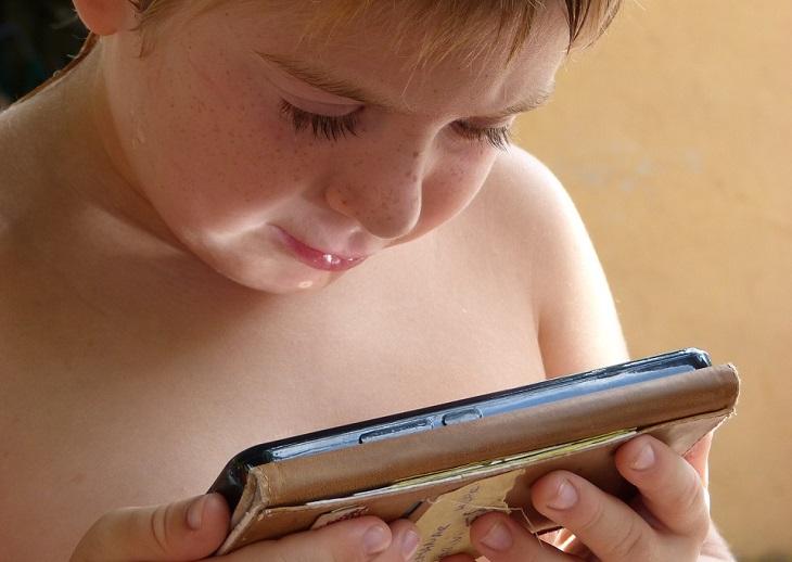 כללים להענשת ילדים: ילד מתבונן בטלפון סלולרי