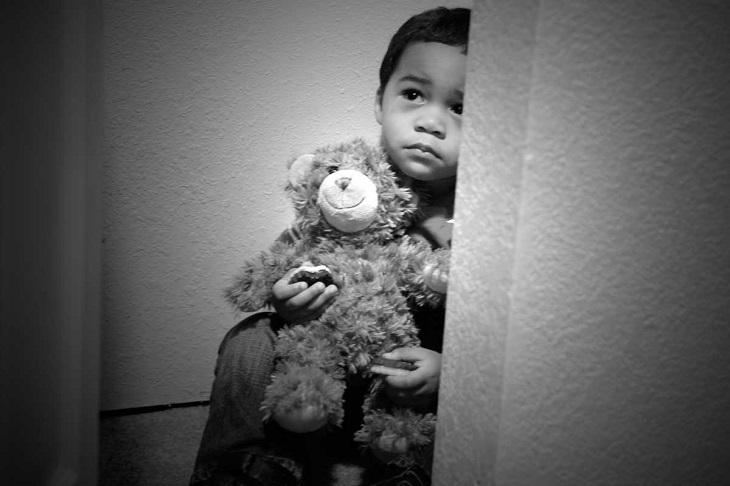 כללים להענשת ילדים: ילד יושב מבויש לצד הקיר, מחזיק דובי צעצוע