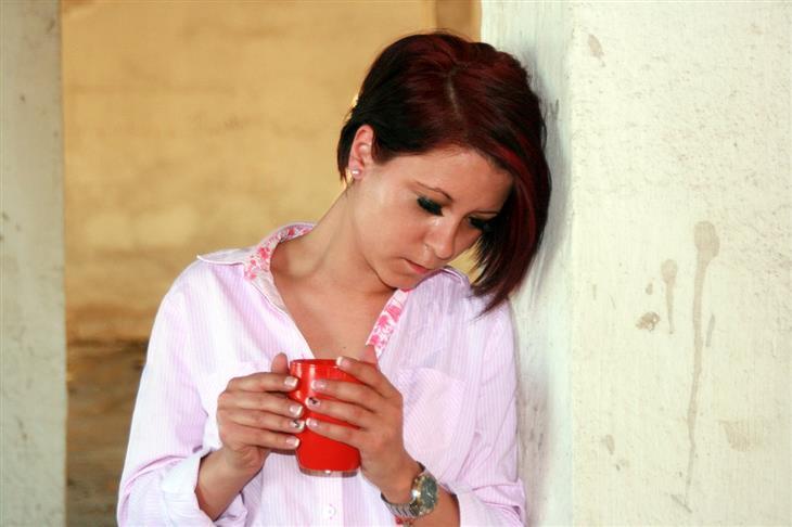 חרדת מערכת יחסים: אישה עם כוס משקה חם מרכינה ראש