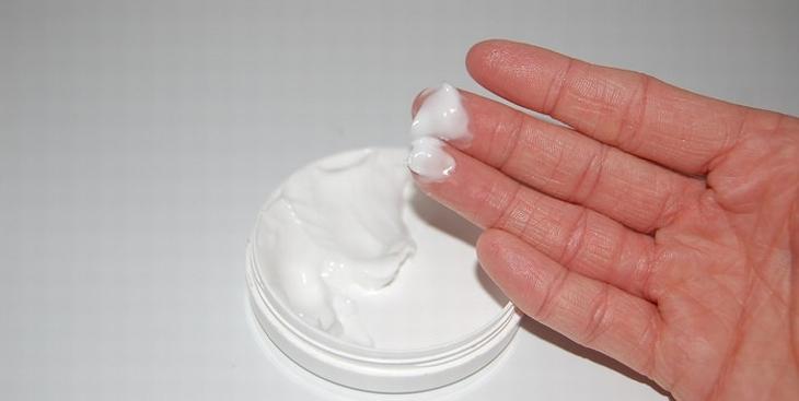 איך להחזיר לידיים מראה צעיר: יד עם קרם על האצבעות