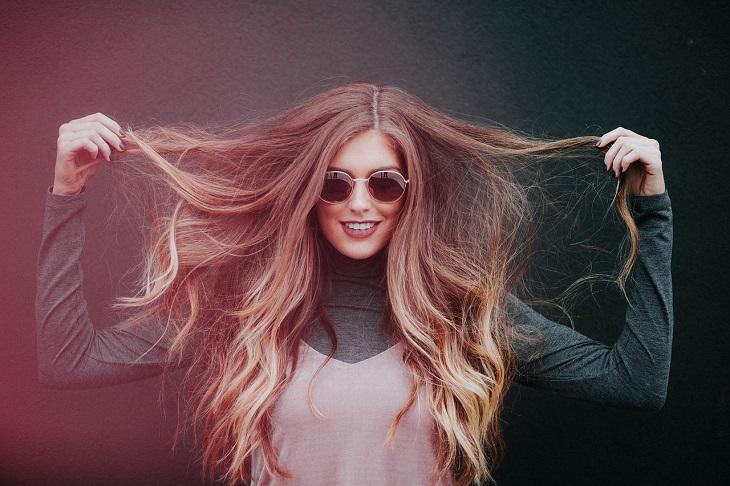 פתרונות טבעיים לשיער פגוע ויבש: אישה מחזיקה בקצוות שיערה