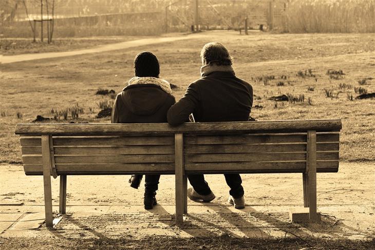 איך להציב גבולות לאנשים: אנשים יושבים על ספסל עם גבם למצלמה