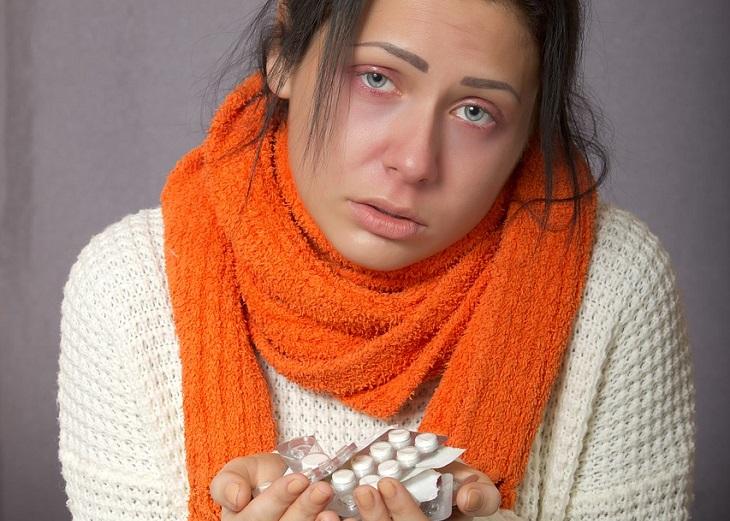 הרגלים רעים שצריך להיפטר מהם כדי לא להסתכן בשפעת: אישה עטופה בצעיף מחזיקה בידיה כדורים