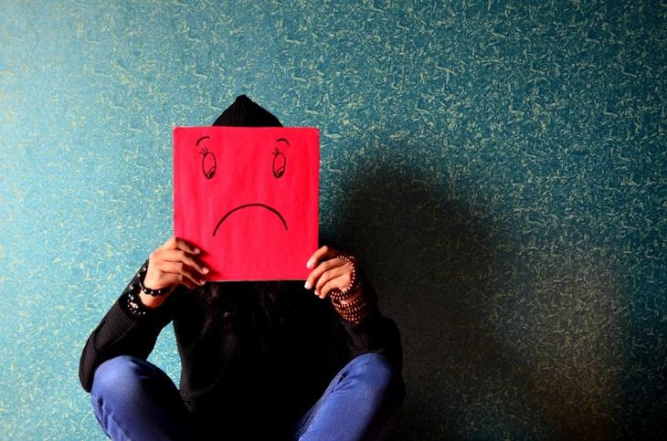 ניתוק קשרים: אדם המחזיק שלט אדום שעליו מצויר פרצוף עצוב, שמסתיר את פניו