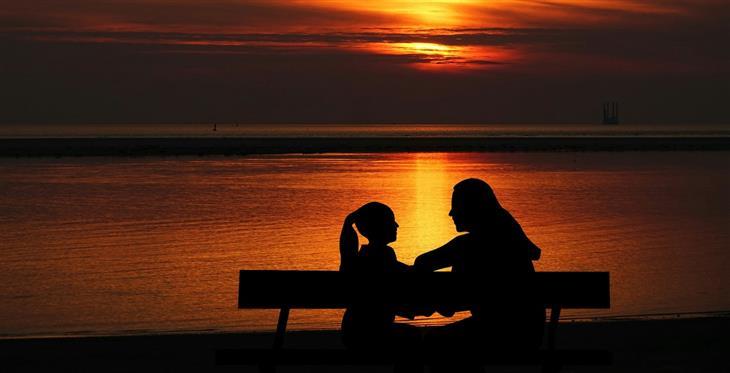 סגנונות הורות: אמא ובת יושבת על ספסל ומדברות מול הים בשקיעה
