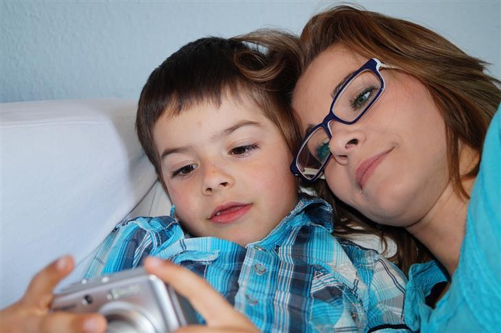 סגנונות הורות: אימא שוכבת לצד בנה והם מסתכלים יחדיו בתמונות במצלמה