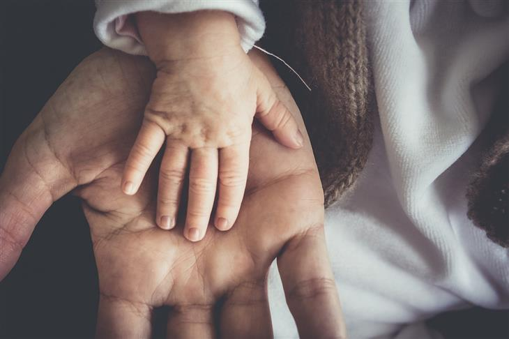סגנונות הורות: יד של תינוק על יד של אדם מבוגר