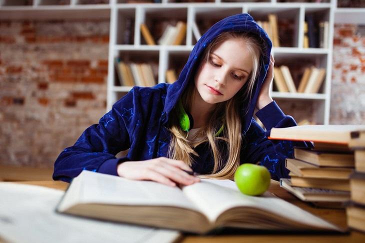 שימוש במריחואנה בקרב בני נוער: נערה יושבת עם קפוצ'ון, מסתכלת על ספר על השולחן תפוח