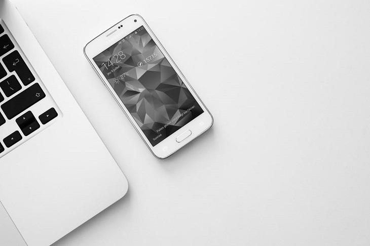 הפחתת שימוש בטלפון חכם: טלפון חכם עם תצוגה אפורה, מונח על שולחן לבן לצד מחשב נייד