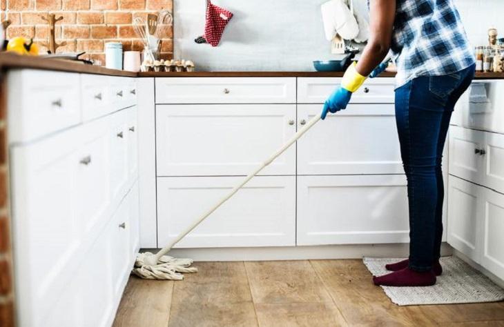 שאלות שהורים צריכים להפסיק לשאול: אישה מנקה במטבח ביתה