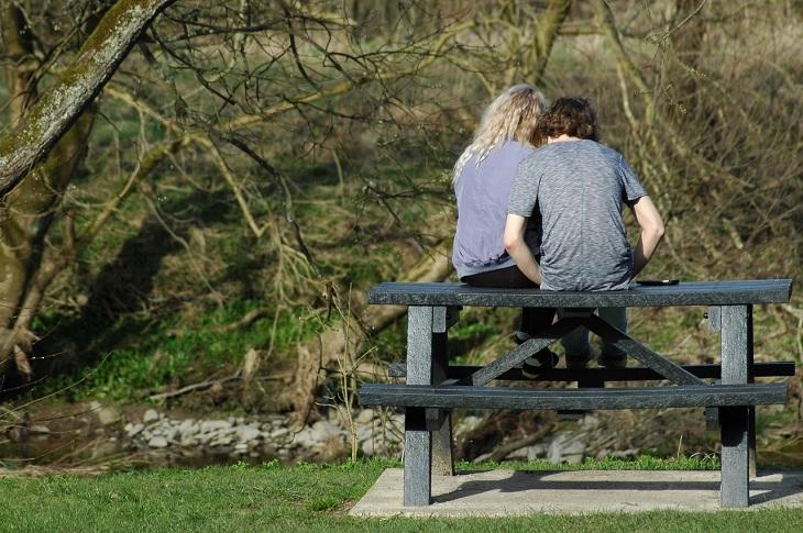 שאלות שהורים צריכים להפסיק לשאול: זוג מתבגרים יושב יחד על שולחן עץ