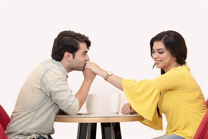 איך נראית זוגיות מאושרת: גבר מנשק כף יד של אישה מול שולחן