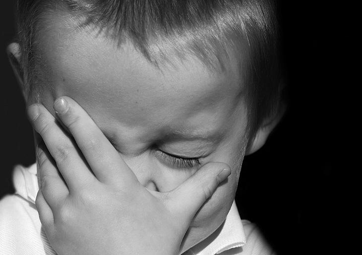 דרכים להתמודדות עם ילדות קשה: ילד תופס את פניו בהבעת עצב