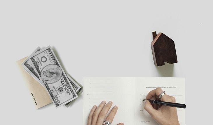 ירושה על פי דין: יד אוחזת בט וכותבת שלצידה דגם עץ של בית וחבילת שטרות