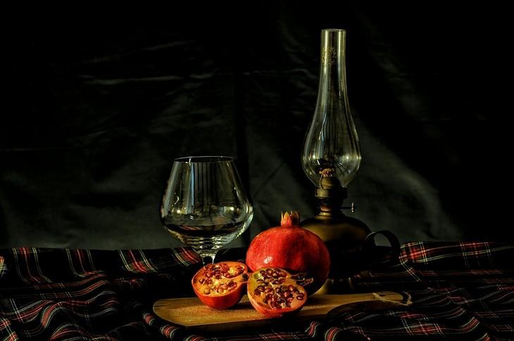 יתרונות בריאותיים של שמן זרעי רימון: רימון חצוי לשניים מונח על קרש חיתוך ומאחוריו כוס ובקבוק זכוכית