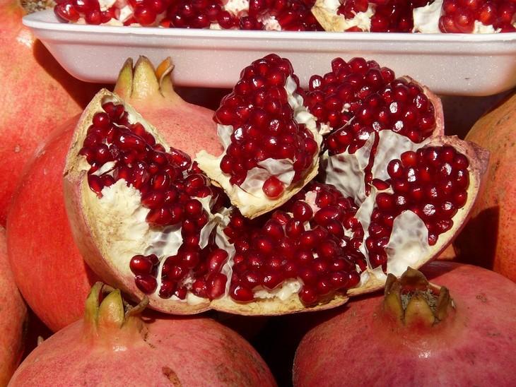 יתרונות בריאותיים של שמן זרעי רימון: חצי רימון פתוח ומתחתיו רימונים סגורים