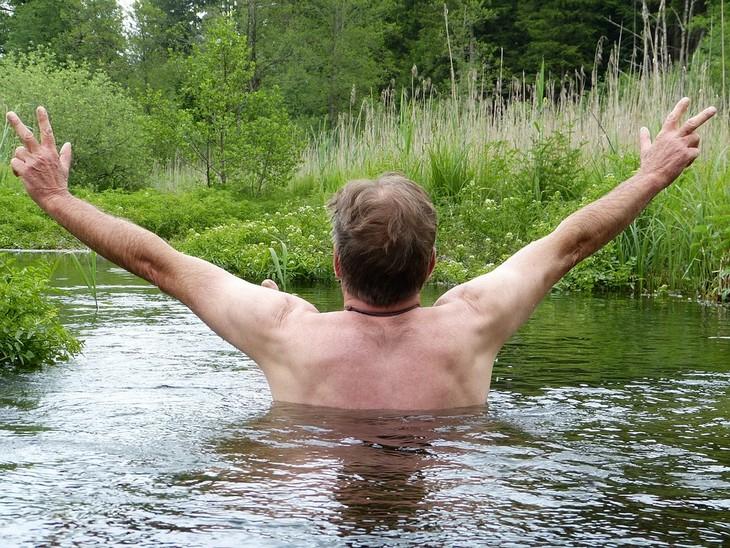 יתרונות בריאותיים של שמן זרעי רימון: גבר נמצא בתוך נחל ומרים את ידיו באוויר