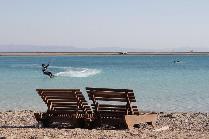 תמונות מסיני: שני כיסאות עץ לצד ים וברקע גבר גולש