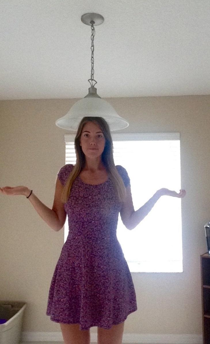בעיות של אנשים גבוהים: בחורה גבוהה עומדת תחת מנורה שמשתלשלת נמוך ומכסה את ראשה