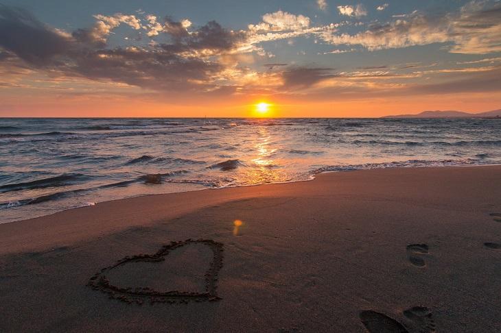 משל הבנאי: זריחה שנשקפת מחוף שעל חולו מצויר לב