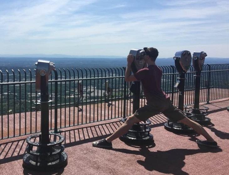 בעיות של אנשים גבוהים: בחור גבוה מבצע שפגט כדי להתבונן במשקפת אל עבר נוף