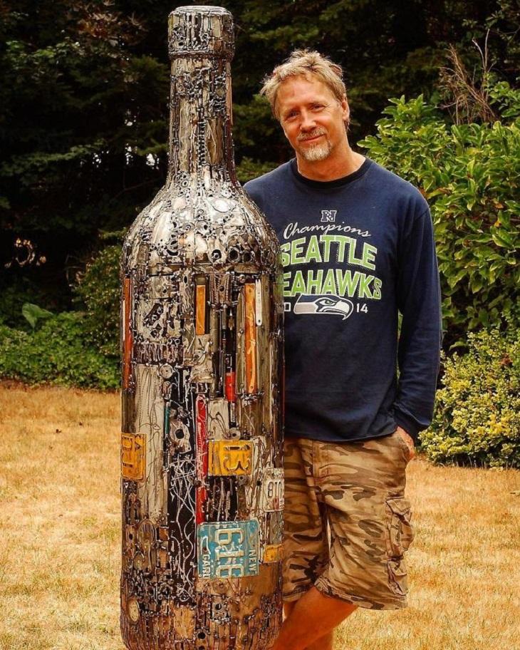פסלים ממתכת ממוחזרת: בריאן מוק עומד לצד בקבוק יין ענקי