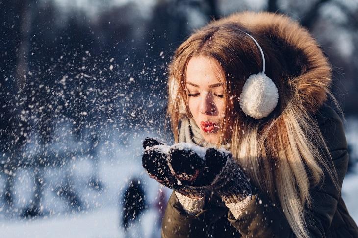 טיפים לאיפור בחורף: אישה נושפת על שלג