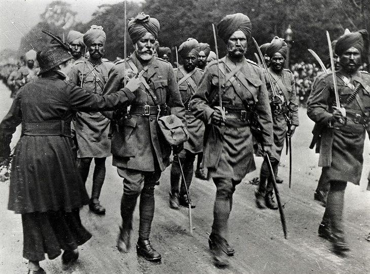 תמונות היסטוריות: חיילים סיקים צועדים ואישה מצמידה לאחד מהם פרח למדים