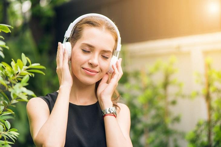 אופטימיות להתמודדות עם חרדה: בחורה מקשיבה למוזיקה דרך אוזניות ומחייכת