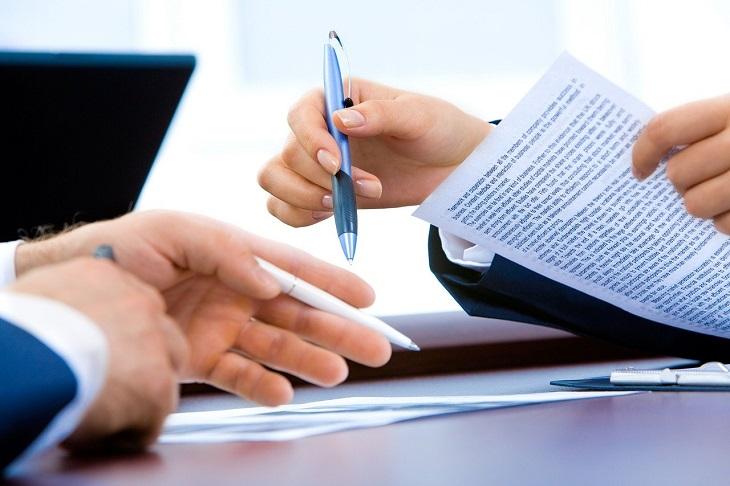 דיני צוואה: ידיים אוחזות בעטים ומסמכים