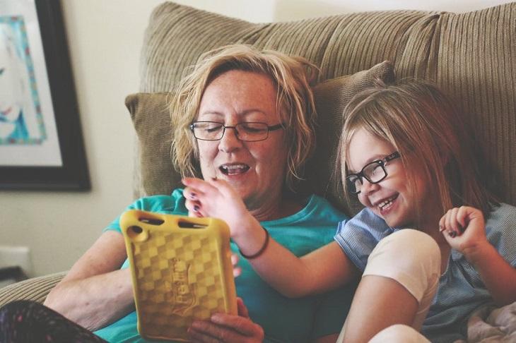 סימנים לזיהוי ילד מחונן: ילדה ואישה מבוגרת משחקות בטאבלט