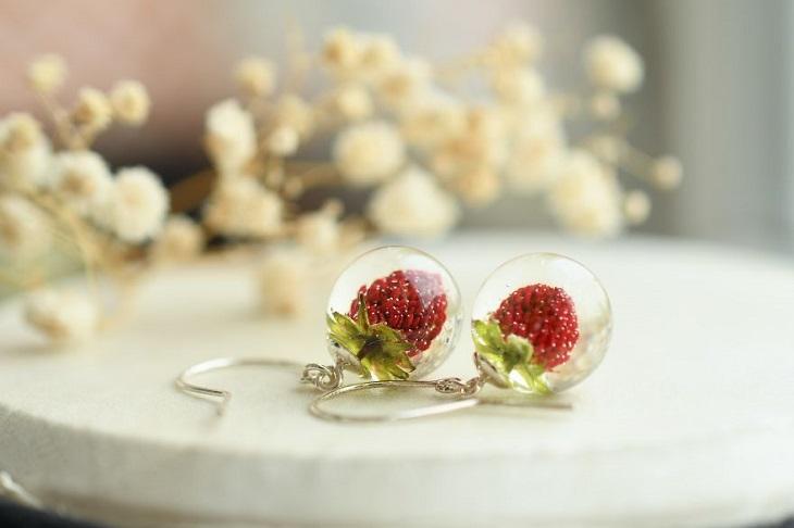 תכשיטים שמכילים פרחים: עגילים עם כדורים שיש בתוכם פטל