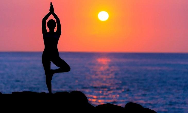 פסיכולוגיה וניו אייג': אישה מבצעת יוגה על רקע שקיעה
