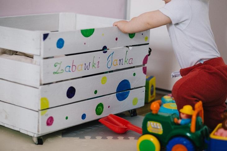 טעויות שפוגעות בשינה של תינוק: תינוק ליד ארז צעצועים, ולידו פזורים צעצועים על הרצפה