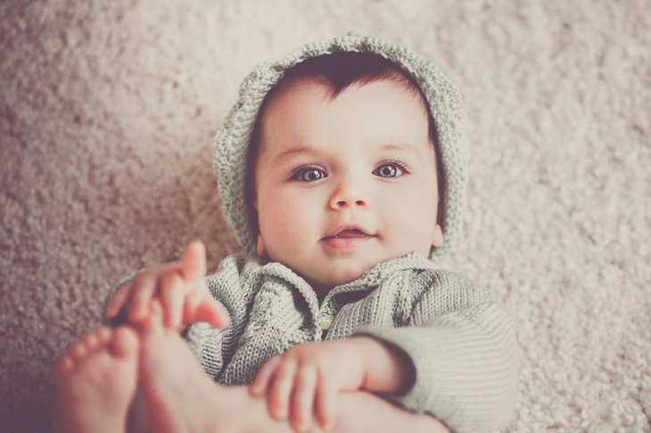 טעויות שפוגעות בשינה של תינוק: תינוק לבוש ושוכב על שטיח