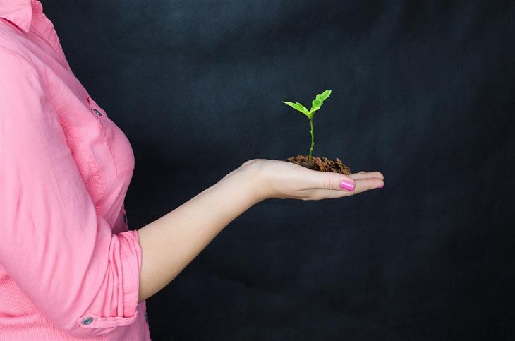 דברים שנורמלי לחוות בתהליך צמיחה אישית: אישה מחזיקה אדמה ובה נבט