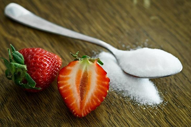 יתרונות וחסרונות באכילת גרעיני חמנייה: כפית עם סוכר שלידה סוכר שהתפזר על השולחן ותותים