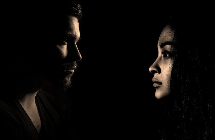 משפטים שפותרים ריבים בזוגיות: גבר עומד מול אישה בחושך