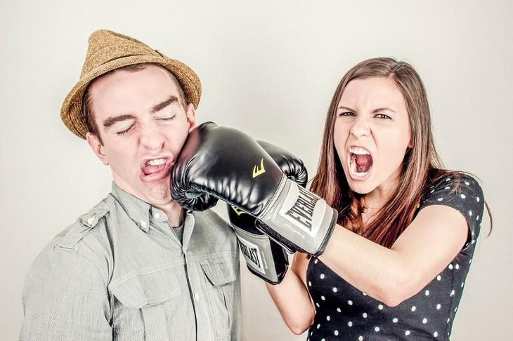 משפטים שפותרים ריבים בזוגיות: אישה עם כפפות אגרוף מרביצה לגבר
