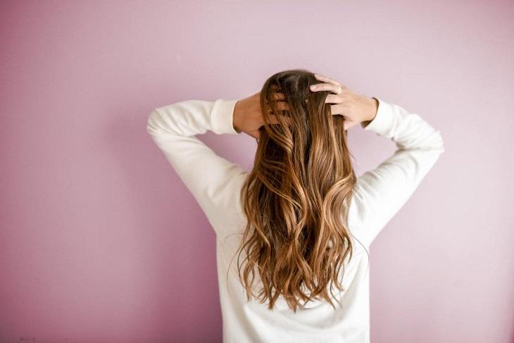 שיער שומני: אישה שנוגעת בשיערה
