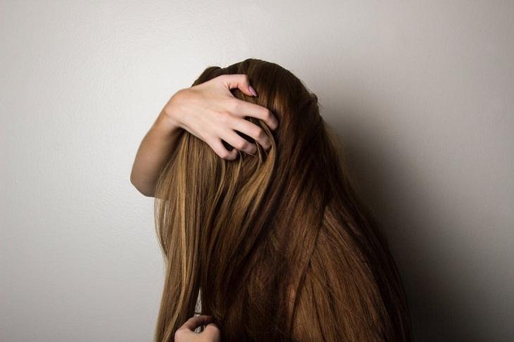 שיער שומני: בחורה נוגעת בשיערה החלק