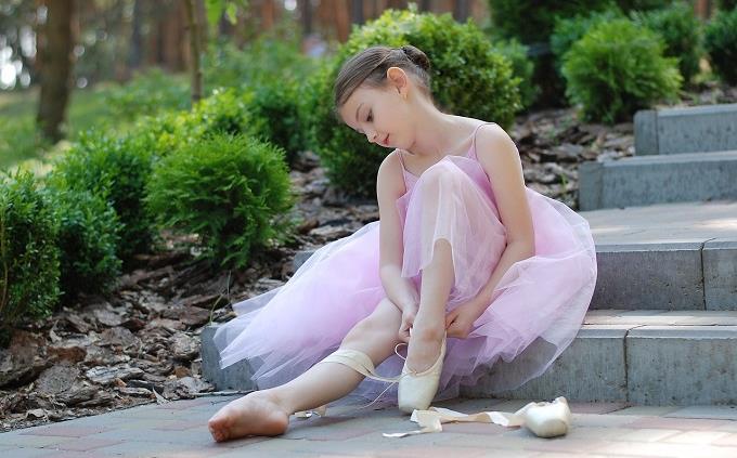 טריווית אנגלית: ילדה קטנה יושבת עם בגדי בלט על המדרגות וקושרת שרוכים בנעליים