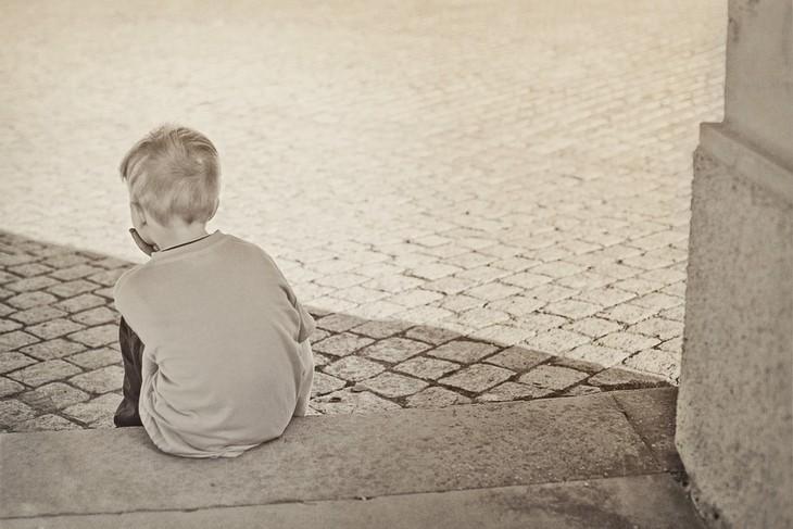 התנהגויות שהן קריאה לעזרה בקרב ילדים: ילד יושב עם הגב למצלמה על שפת מדרכה