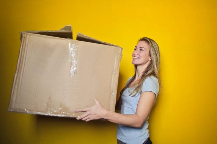 טיפים לקניות ומעבר דירה: אישה סוחבת קופסה גדולה