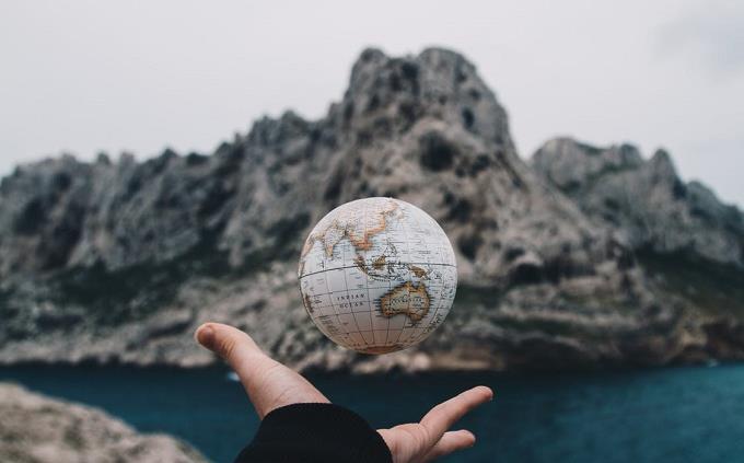טריווית אנגלית: יד זורקת כדור בצורת הגלובוס, על נוף של הרים ואגמים