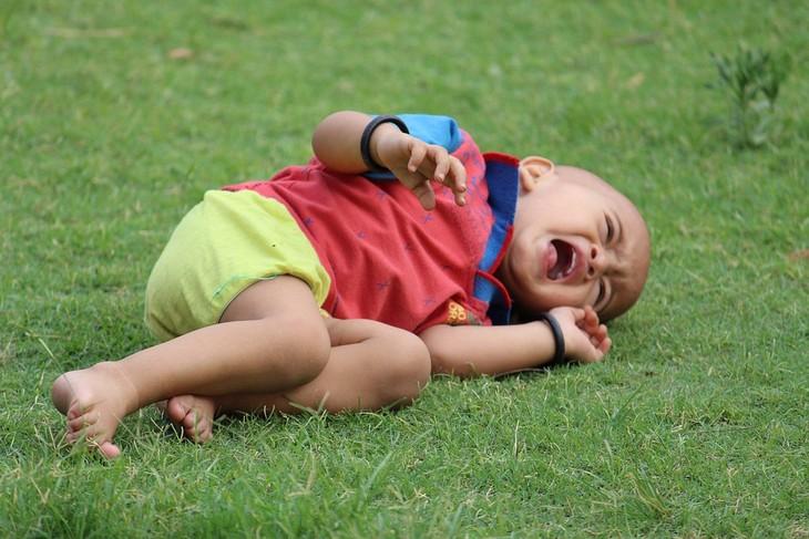 התנהגויות שהן קריאה לעזרה בקרב ילדים: ילד שוכב על דשא ובוכה