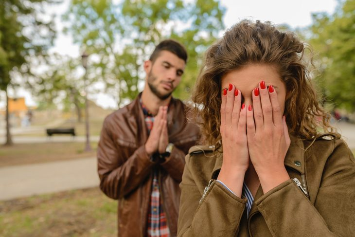 איך להקשיב בלי להתגונן: גבר מתחנן לאישה שתקשיב לו בעוד שהיא מכסה את פניה בידיה