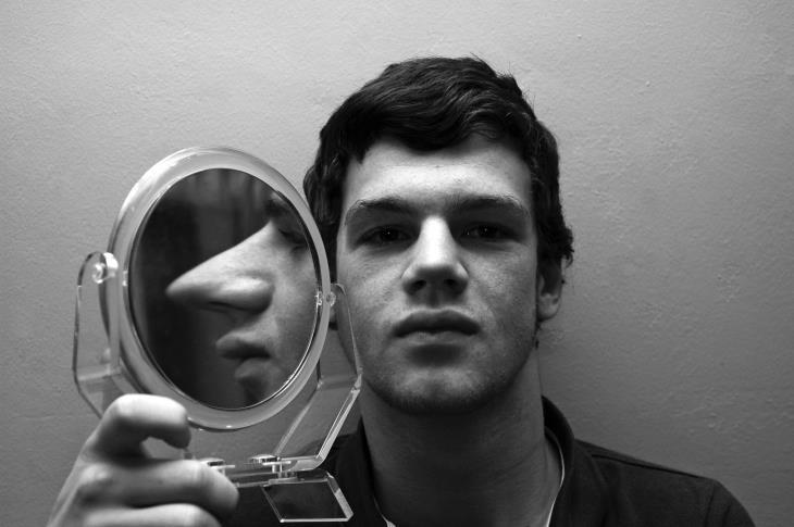 איך לזהות נוכלים: איש מחזיק מראה לצד פניו, ועליה הוא משתקף עם אף ארוך