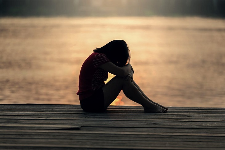 השפעה של זוגיות רעילה על ילדים: אישה יושב עצובה על מזח