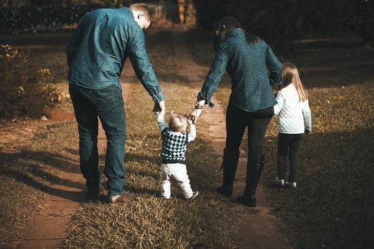 טיפים להפוך בן בכור לאח: הורים הולכים בפארק עם תינוק וילדה קטנה
